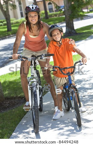 A young African American woman & boy child, mother & son, riding bicycles in the summer