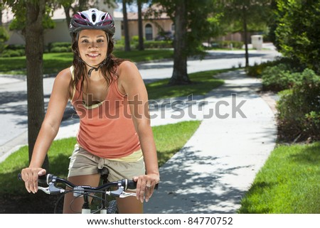 A young African American woman riding a bicycle in the summer. - stock photo