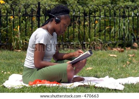 A young african american woman sits in the park and reads while listening to music.