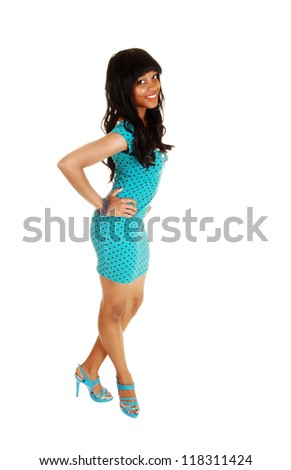 A young African American woman standing for white background with her long curly black hair and a tight turquoise dress and high heels. - stock photo