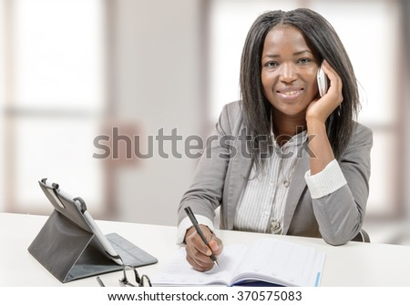 a young african american woman writing, and giving a call with mobile phone