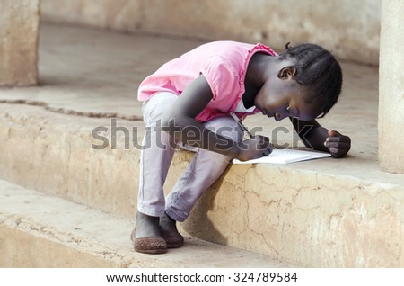 A young African girl writing her lesson on an exercise book. Little black baby teenage child learning and studying outside her classroom repeating her lesson. - stock photo