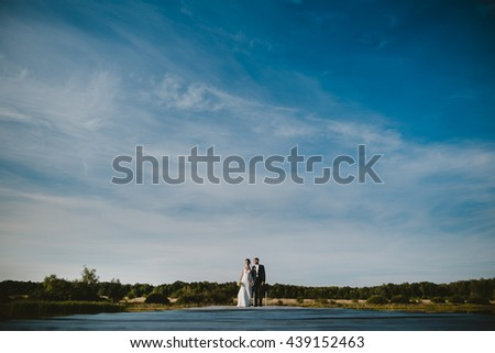 a young amazing  couple standing against a background of lake