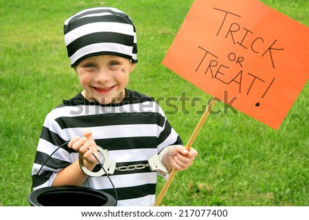 A young American child is dressed up in a prisoner costume on Halloween, getting ready to go trick-or-treating. - stock photo