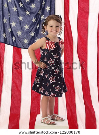 A young American girl in patriotic dress with American flag - stock photo
