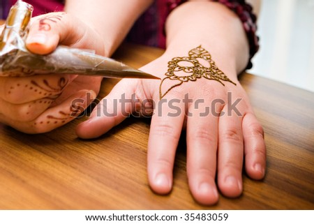 A young american woman gets henna applied to her hands - stock photo