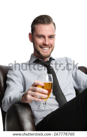 A young and attractive businessman sitting down after work with a cold beer, relaxing in a couch wearing a shirt and tie. White background. - stock photo