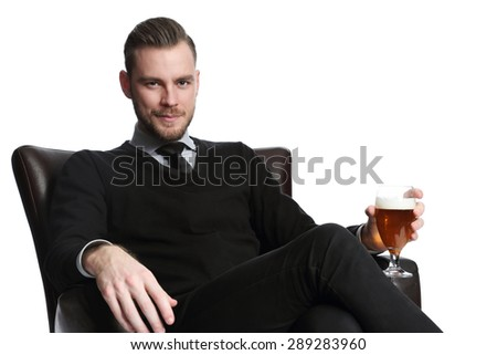 A young and attractive businessman sitting down after work with a cold beer, relaxing in a couch wearing a pullover, shirt and tie. White background. - stock photo