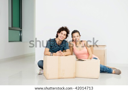 A young and attractive couple with boxes of belongings in their new home