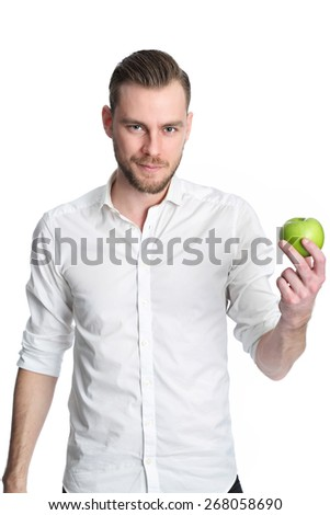 A young and attractive man in his 20s standing wearing a white shirt and holding a green apple, living a healthy lifestyle. White background. - stock photo