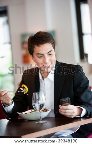 A young and attractive man uses his phone while eating a salad in an indoor restaurant