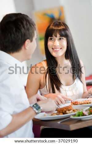 A young and attractive woman dining with her partner in an indoor restaurant