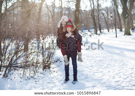 A young and beautiful couple is having fun in the park. Valentine's Day and love story concept. Winter season.