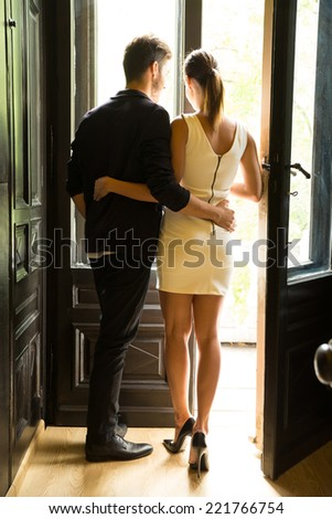 A young and beautiful couple standing at the window. - stock photo