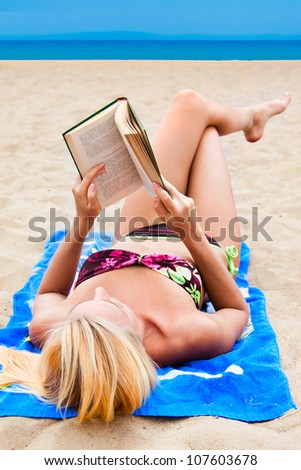 A young and beautiful woman resting on a beach reading a book in hard cover green - stock photo