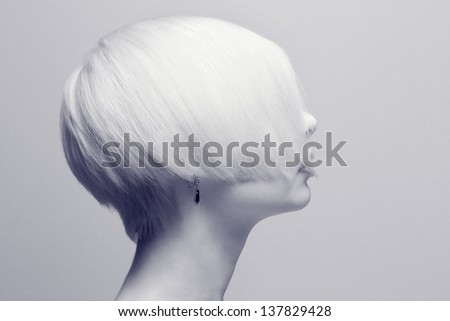 A young and cool fashion female with creative hair style. Natural retouched in black and white with a blue tone. - stock photo