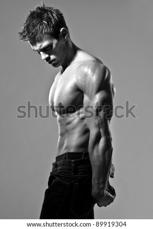 a young and fit male model posing his muscles - stock photo
