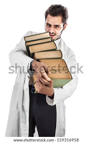 a young and handsome doctor or medical student carrying a pile of ancient book - stock photo