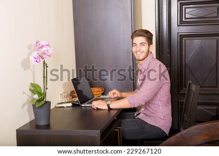 A young and handsome man using a laptop computer in a asian styled hotel room.  - stock photo