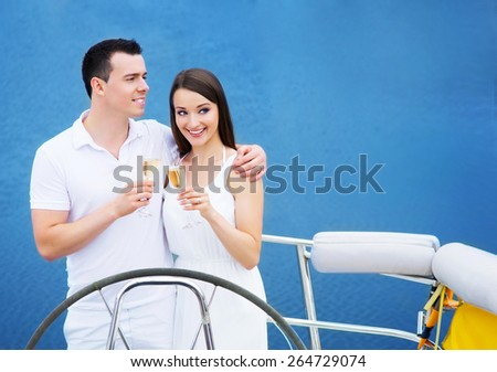 A young and happy Caucasian couple drinking champagne on a boat in the sea. - stock photo