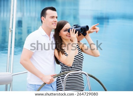 A young and happy Caucasian  couple relaxing on a boat and looking through binoculars. - stock photo