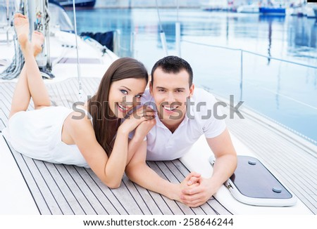 A young and happy Caucasian couple relaxing together on a boat trip. - stock photo
