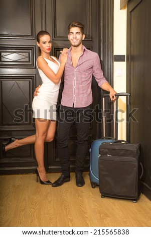 A young and happy couple arriving to their Hotel room. - stock photo