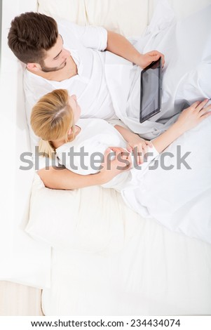 A young and happy couple with a Tablet PC  in Bed.