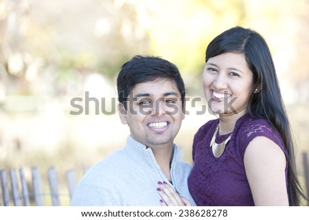 A young and happy Indian couple portrait with a Fall background on a sunny day. - stock photo