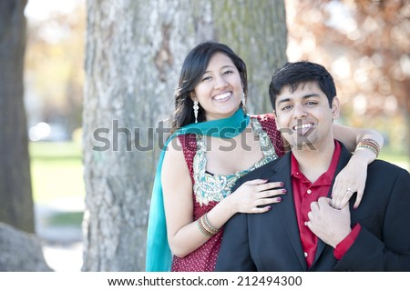 A young and happy Indian couple posing by a tree in the Fall on a sunny day. - stock photo