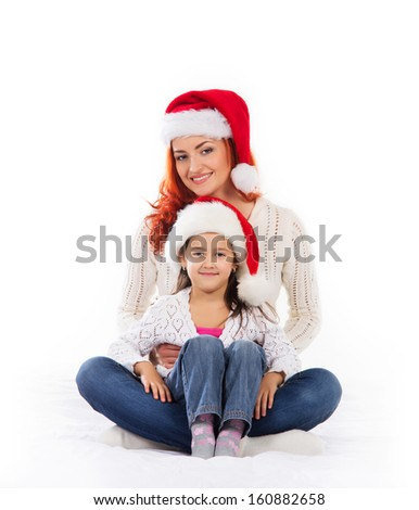A young and happy mother and daughter in Christmas hats - stock photo