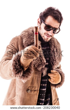 a young and rich man wearing a sheepskin coat isolated over a white background holding a cigar - stock photo