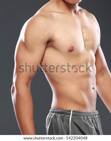 a young and sexy male model posing his muscles - stock photo