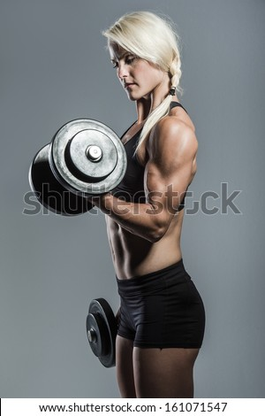 a young and very fit woman training with dumbells