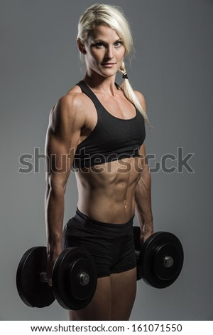 a young and very fit woman training with dumbells - stock photo