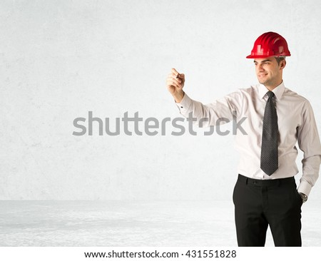 A young architect in red safety helmet planning and drawing with a pen in his hand in empty space in front of a white background. - stock photo