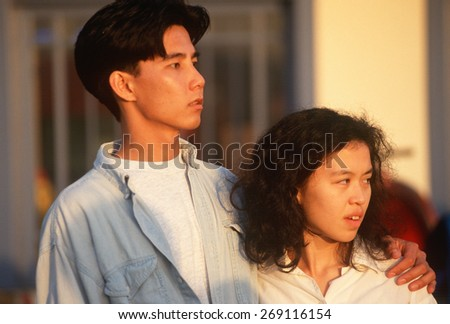 A young Asian-American couple watching the sunset, Los Angeles, CA - stock photo
