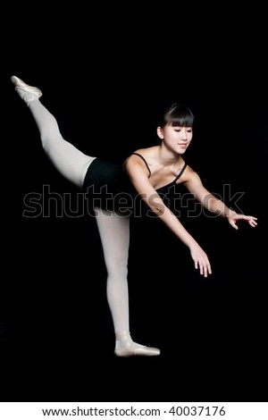 A young asian ballerina doing a ballet pose against black background - stock photo