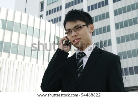 A young Asian business executive speaking on a cellphone - stock photo