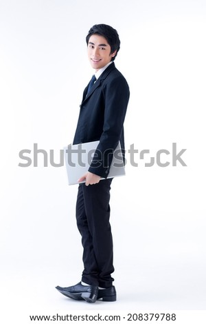 A young asian business man standing with laptop  - stock photo