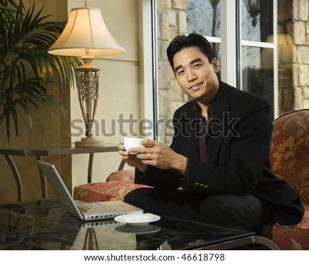 A young Asian businessman holds a coffee cup while seated at his laptop. Horizontal shot.