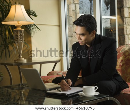 A young Asian businessman looking at a laptop computer whiles taking notes on a notebook. Horizontal shot.