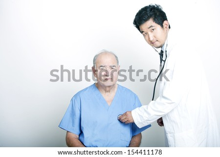 A young Asian Doctor comforting a Senior adult patient - stock photo