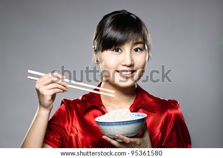 A young Asian girl eating rice with bowl and chopsticks - stock photo
