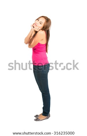 A young Asian girl with brown hair, pink tank top looking at camera assumes a cute pose with elbows against body and hands tucked under her chin - stock photo