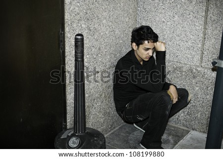 A young asian guy is squatting in a corner, his arm supporting his head and thinking/Portrait of a young asian guy