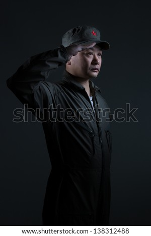 A young Asian man in a communist military scenario saluting - stock photo