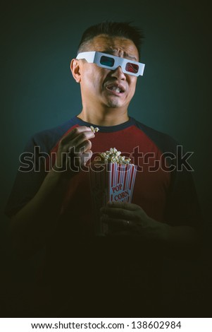 A young Asian man  in an entertainment setting with 3D glasses watching a horror movie - stock photo
