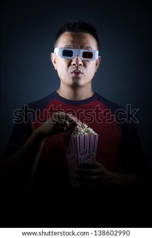 A young Asian man  in an entertainment setting with popcorn. - stock photo