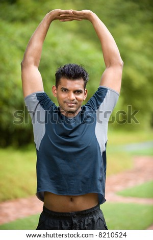A young Asian man in sportswear stretching outside